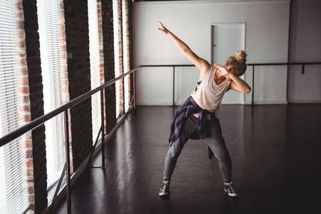 move in: Woman performing dab dance move in dance studio LANG_EVOIMAGES