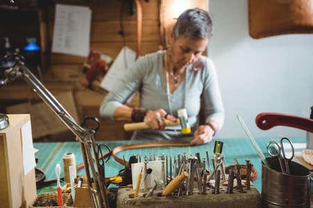 hammering: Craftswoman hammering leather in workshop