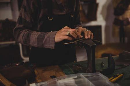 hammering: Mid-section of craftswoman hammering leather in workshop LANG_EVOIMAGES