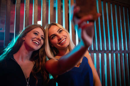 Happy friends taking selfie from mobile phone in bar LANG_EVOIMAGES