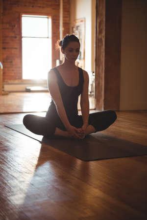 konasana: Woman practising yoga in fitness studio LANG_EVOIMAGES