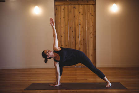 side angle pose: Woman practising yoga in fitness studio LANG_EVOIMAGES
