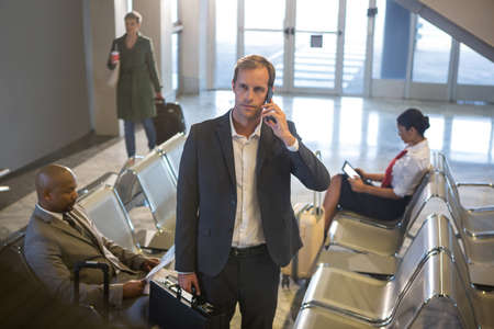 businessman waiting call: Businessman with briefcase talking on his phone while standing at airport terminal