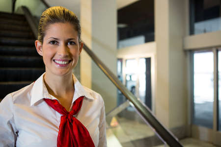 Portrait of smiling female staff standing on escalator in airport