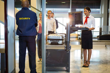 airport security: Airport security guard with passenger walking through body scanner at airport terminal