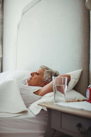 ageing process: Senior woman sleeping on bed in bedroom at home LANG_EVOIMAGES