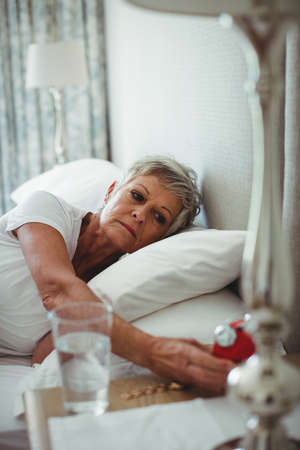 turning off: Senior woman lying on bed and turning off an alarm clock in bedroom at home