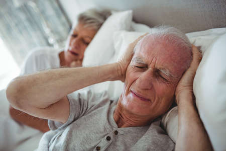 hands covering ears: Senior man lying on bed and covering his ears with hands in bedroom LANG_EVOIMAGES