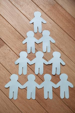 human pyramid: outs corte del papel que forman la pirámide humana sobre la mesa de madera Foto de archivo