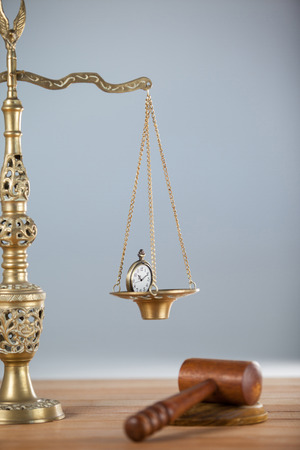 Conceptual image of pocket watch on justice scale and a wooden hammer