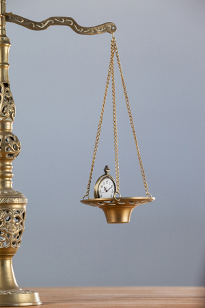 Conceptual image of pocket watch on justice scale