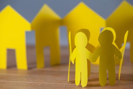 Conceptueel beeld van papierknipsel mensen die in een cirkel tegen papierhuizen staan