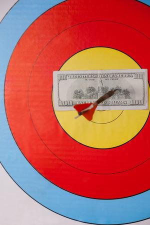 Close-up of darted hundred dollars on dart board