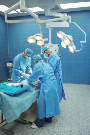 surgical tray: Team of surgeons performing operation in operation theater at hospital Stock Photo