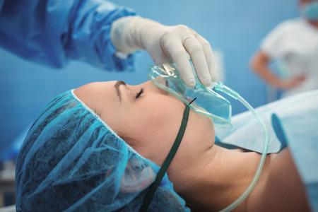 Cirujano ajustar máscara de oxígeno en la boca del paciente en el quirófano en el hospital
