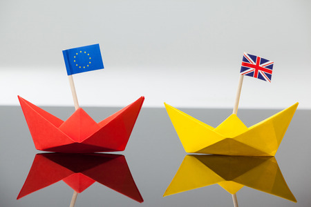 Close-up of two paper boats with union jack and european union flag