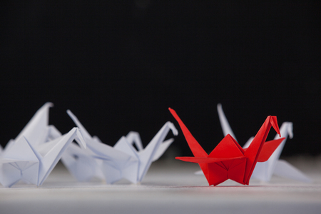 Paper cranes arranged together on white surface Stock Photo