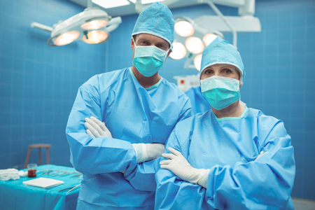 Portrait of male and female surgeon standing with arms crossed in operation theater at hospital