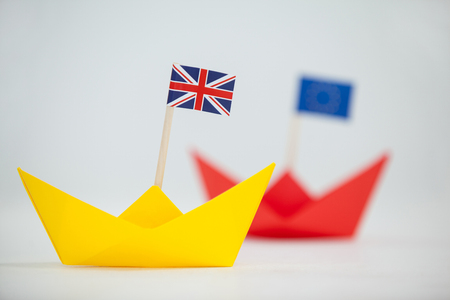 withdrawal: Close-up of yellow paper boat with union jack flag
