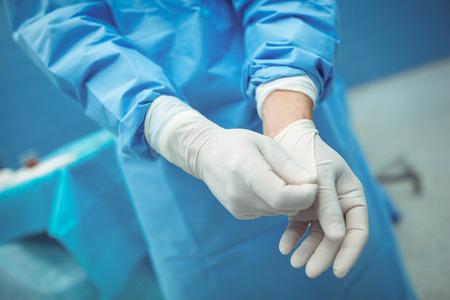 Chirurgien masculin enlevant des gants chirurgicaux en fonctionnement au théâtre à l'hôpital Banque d'images - 69180009