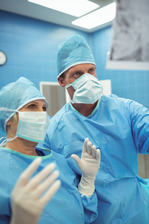 Male and female surgeons interacting in operation theater at hospital