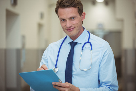 Portrait of male doctor writing on clipboard in corridor at hospital