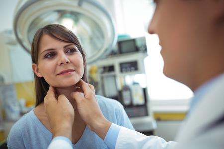 병원에서 여성 환자 목을 검사하는 의사