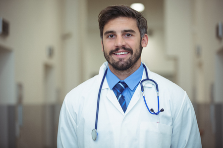 operative: Portrait of male doctor standing in corridor at hospital