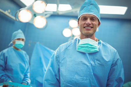 Portrait of male surgeon smiling in operation theater at hospital Stock Photo