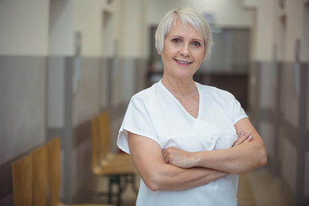 Portrait of female nurse standing with arms crossed in corridor at hospital Stock Photo