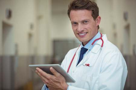 Portrait of male doctor using digital tablet in corridor at hospital