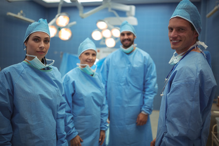operative: Portrait of surgeons standing in operation theater at hospital Stock Photo