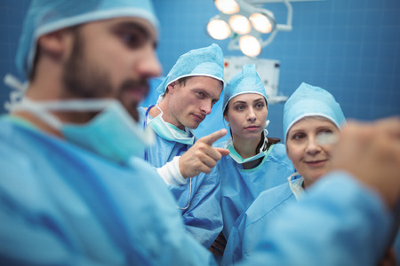 Team of surgeons having discussion in operation theater at hospital