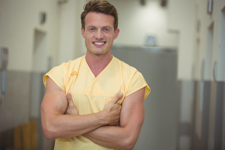 Portrait of male nurse standing with arms crossed in corridor at hospital Stock Photo