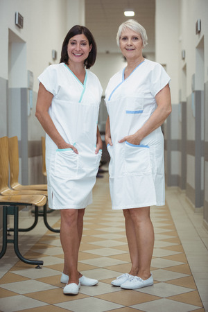 Portrait of two female nurse standing in corridor at hospital Stock Photo
