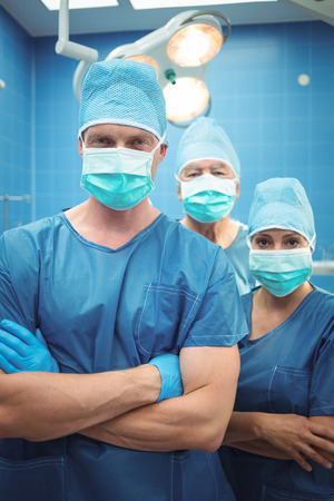 Team of surgeons standing with arms crossed in operation theater at hospital