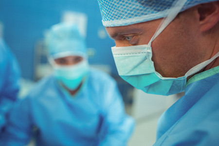 operative: Male surgeon wearing surgical mask in operation theater at hospital