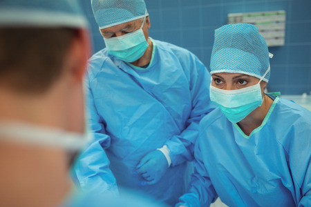 Team of surgeons performing operation in operation theater at hospital Stock Photo