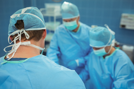 operative: Team of surgeons performing operation in operation theater at hospital Stock Photo