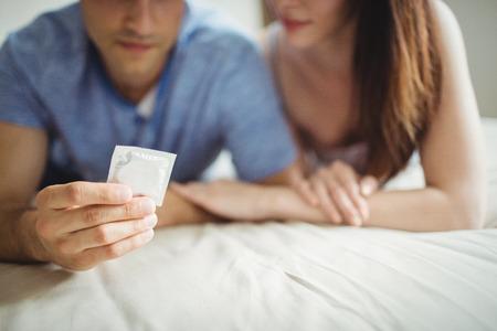 Close-up van het paar met een condoom op bed in de slaapkamer