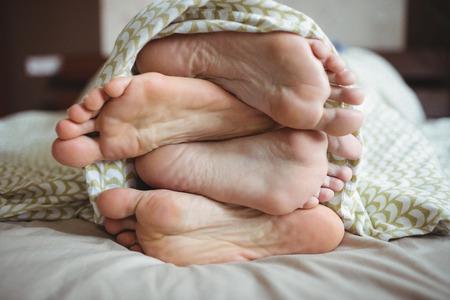 Paar zeigen ihre Füße, während auf einem Bett im Schlafzimmer liegend Standard-Bild