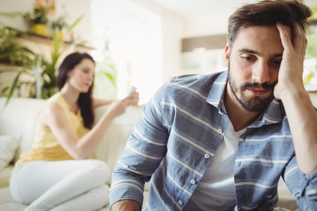 ignoring: Upset couple ignoring each other on sofa in living room Stock Photo