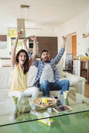 pareja viendo tv: Excited couple watching tv together in living room at home