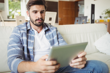 Man using digital tablet while relaxing on sofa in the living room