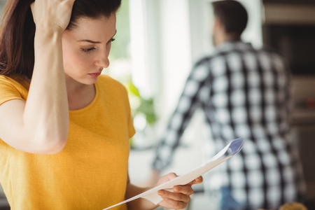 tensed: Tensed woman checking bill in kitchen at home