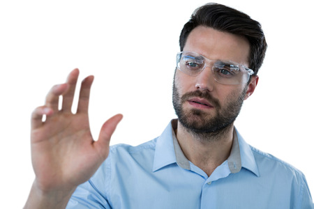 invisible object: Man wearing protective eyewear pretending to touch an invisible object against white background Stock Photo