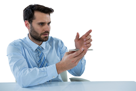 invisible object: Businessman pretending to touch an invisible object at desk against white background