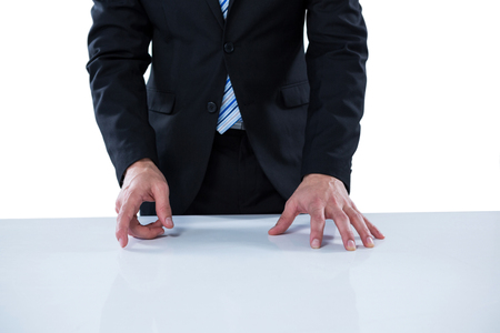 invisible object: Businessman pretending to touch an invisible object against white background Stock Photo