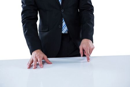 invisible: Businessman pretending to touch an invisible object against white background Stock Photo