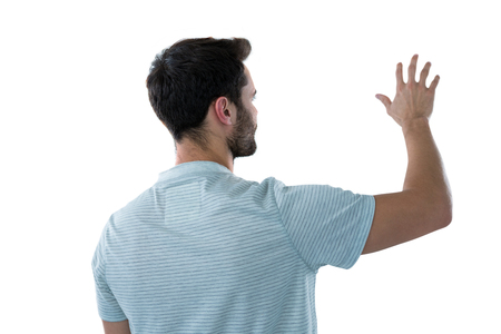 invisible object: Rear view of man pretending to touch an invisible object Stock Photo